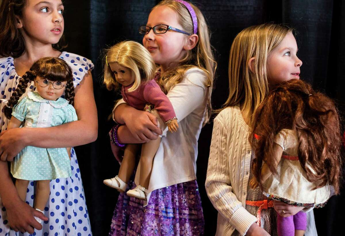 Participants await their turn on the runway from backstage during the eighth annual American Girl Fashion Show Saturday, March 22, 2014, at the The Golf Club at Newcastle in Newcastle, Wash. This year, the event raised an estimated 100,000 dollars for Seattle Children's Hospital.