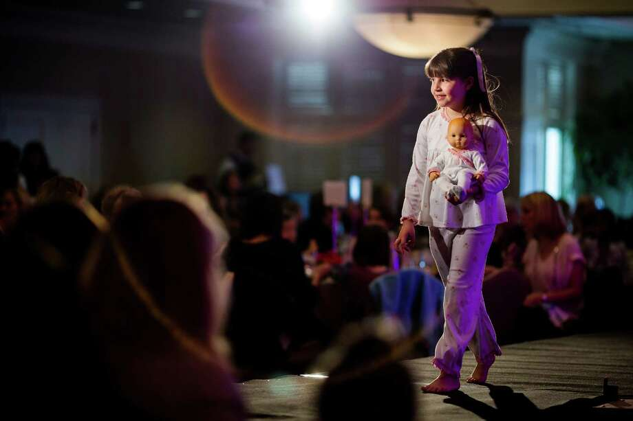 Strutting the runway, young women show off their knack for matching garb and doll during the eighth annual American Girl Fashion Show Saturday, March 22, 2014, at the The Golf Club at Newcastle in Newcastle, Wash. This year, the event raised an estimated 100,000 dollars for Seattle Children's Hospital. Photo: JORDAN STEAD, SEATTLEPI.COM / SEATTLEPI.COM
