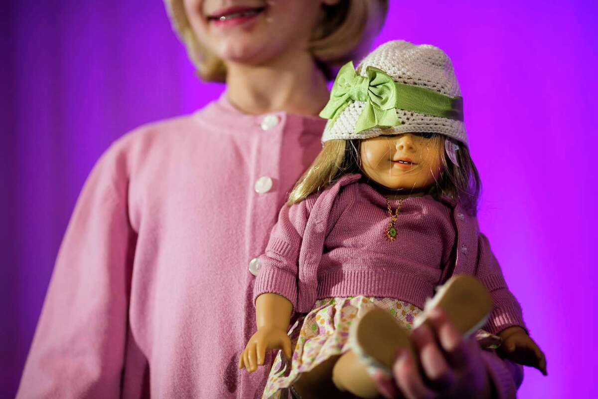 Young women show off their matching garb and dolls during the eighth annual American Girl Fashion Show Saturday, March 22, 2014, at the The Golf Club at Newcastle in Newcastle, Wash. This year, the event raised an estimated 100,000 dollars for Seattle Children's Hospital.