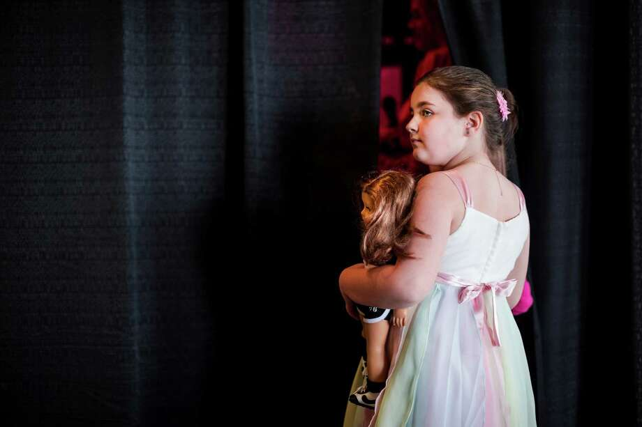 A young participant awaits her turn on the runway from backstage during the eighth annual American Girl Fashion Show Saturday, March 22, 2014, at the The Golf Club at Newcastle in Newcastle, Wash. This year, the event raised an estimated 100,000 dollars for Seattle Children's Hospital. Photo: JORDAN STEAD, SEATTLEPI.COM / SEATTLEPI.COM