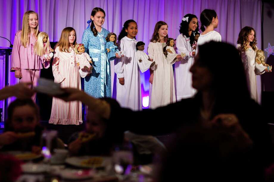 A line of young women show off their knack for matching garb with dolls during the eighth annual American Girl Fashion Show Saturday, March 22, 2014, at the The Golf Club at Newcastle in Newcastle, Wash. This year, the event raised an estimated 100,000 dollars for Seattle Children's Hospital. Photo: JORDAN STEAD, SEATTLEPI.COM / SEATTLEPI.COM