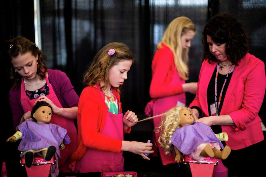 "Dressed in red and pink, Rianna Poch, center, and Kristen DeFranco, right, along with other cheerful young ladies, carefully brush hair and touch up blemishes on plastic models in the ""Doll Hair Salon"" during the eighth annual American Girl Fashion Show Saturday, March 22, 2014, at the The Golf Club at Newcastle in Newcastle, Wash. This year, the event raised an estimated 100,000 dollars for Seattle Children's Hospital. Photo: JORDAN STEAD, SEATTLEPI.COM / SEATTLEPI.COM"
