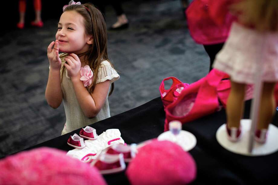 Abbie Lacina, 7, finds herself having a tough time deciding what piece of clothing she wants next for her doll during the eighth annual American Girl Fashion Show Saturday, March 22, 2014, at the The Golf Club at Newcastle in Newcastle, Wash. This year, the event raised an estimated 100,000 dollars for Seattle Children's Hospital. Photo: JORDAN STEAD, SEATTLEPI.COM / SEATTLEPI.COM