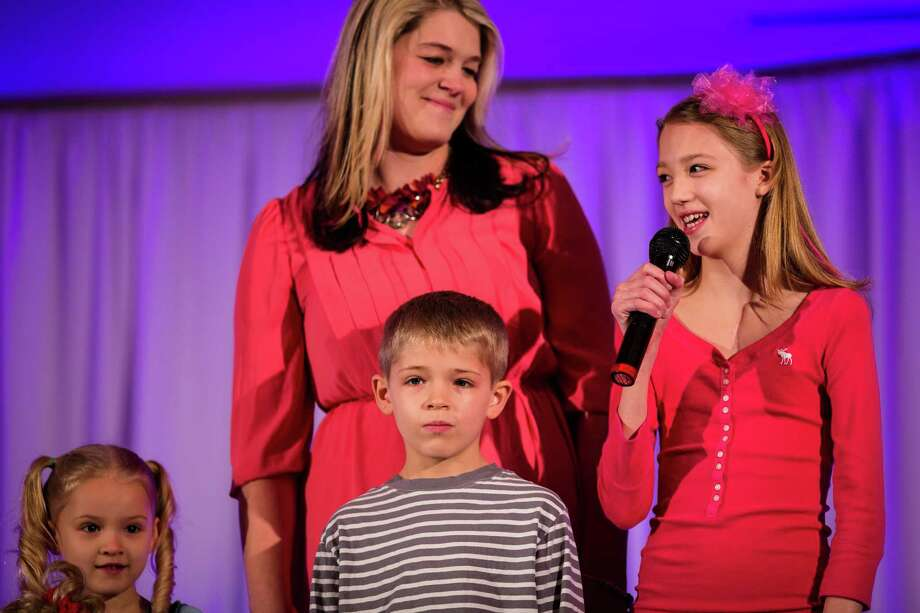 A recipient of aid from Seattle Children's Hospital speaks to the crowd during the eighth annual American Girl Fashion Show Saturday, March 22, 2014, at the The Golf Club at Newcastle in Newcastle, Wash. This year, the event raised an estimated 100,000 dollars for Seattle Children's Hospital. Photo: JORDAN STEAD, SEATTLEPI.COM / SEATTLEPI.COM