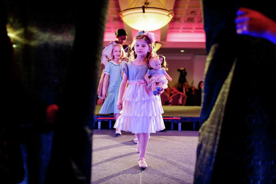 Dolls underarm, the well-dressed young ladies of the eighth annual American Girl Fashion Show leave the stage Saturday, March 22, 2014, at the The Golf Club at Newcastle in Newcastle, Wash. This year, the event raised an estimated 100,000 dollars for Seattle Children's Hospital. Photo: JORDAN STEAD, SEATTLEPI.COM / SEATTLEPI.COM
