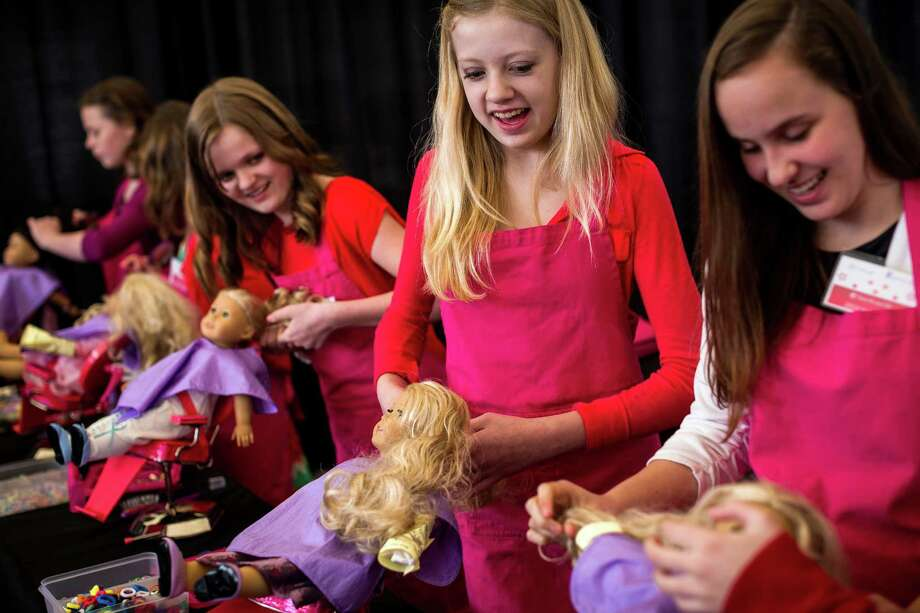"Corrine Booth, center right, carefully brushes hair and touches up blemishes on plastic models in the ""Doll Hair Salon"" during the eighth annual American Girl Fashion Show Saturday, March 22, 2014, at the The Golf Club at Newcastle in Newcastle, Wash. ""When it's your only hope, you've got to do what you've gotta to do,"" Booth said, in regards to damage repair on the dolls. This year, the event raised an estimated 100,000 dollars for Seattle Children's Hospital. Photo: JORDAN STEAD, SEATTLEPI.COM / SEATTLEPI.COM"
