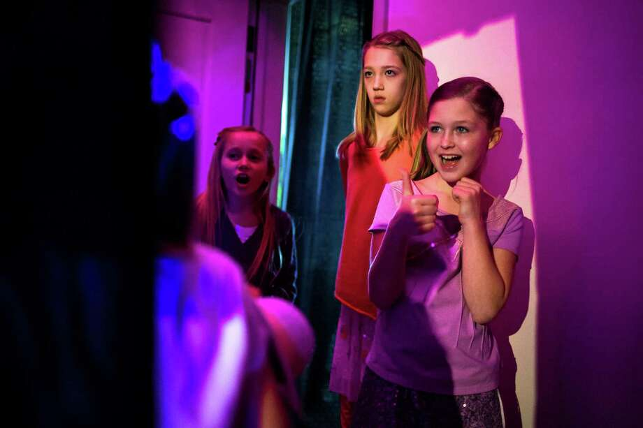 Backstage, girls congratulate each other following successful runway walks with their dolls during the eighth annual American Girl Fashion Show Saturday, March 22, 2014, at the The Golf Club at Newcastle in Newcastle, Wash. This year, the event raised an estimated 100,000 dollars for Seattle Children's Hospital. Photo: JORDAN STEAD, SEATTLEPI.COM / SEATTLEPI.COM