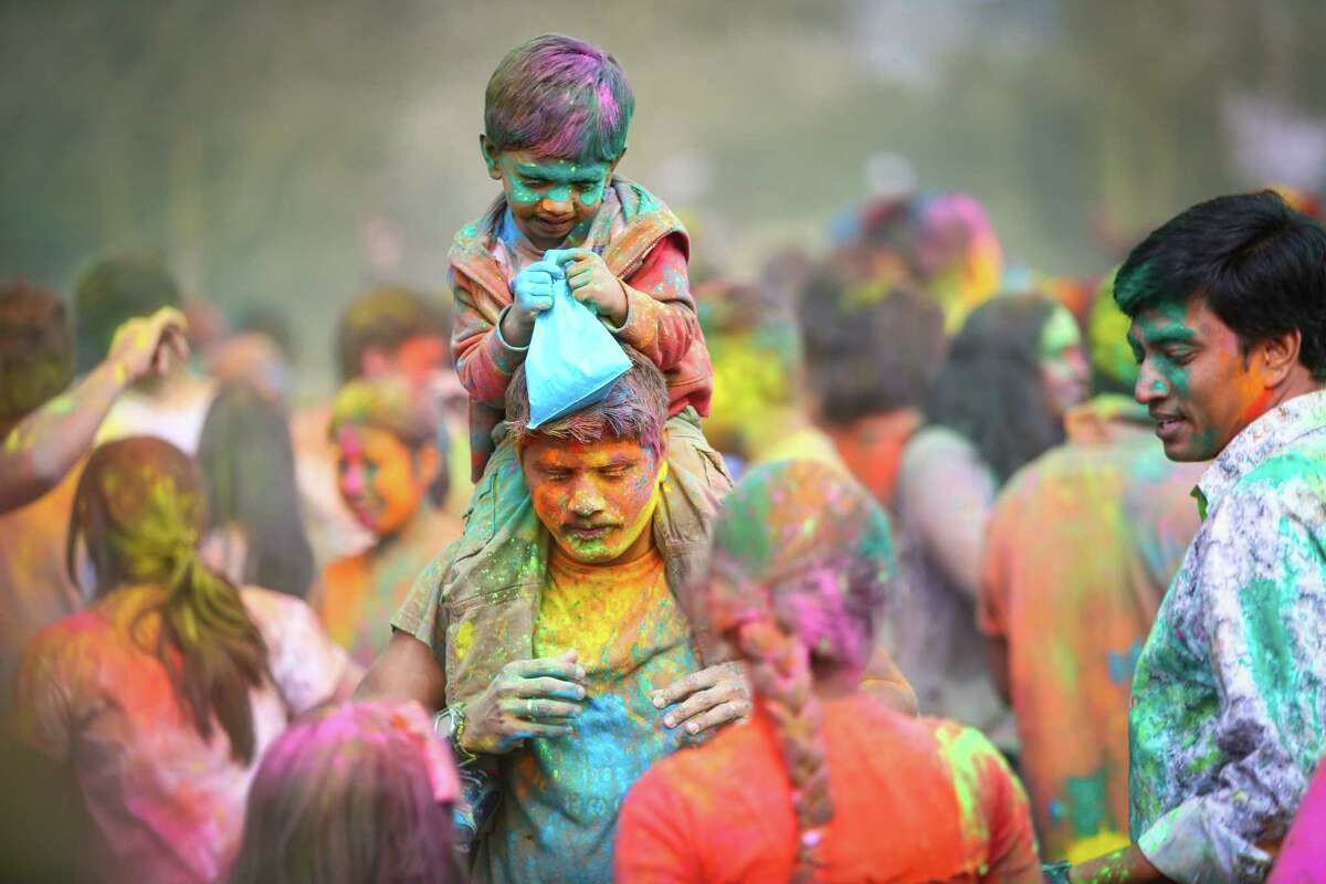 A young participate gets a ride through the crowd during the annual Holi celebration organized by the group Child Rights and You. The annual event celebrates the Indian festival of color and is a fundraiser for CRY. Holi recognizes the coming of spring with colored powder that people throw on each other. Photographed on Saturday, March 22, 2014 at Downtown Park in Bellevue.