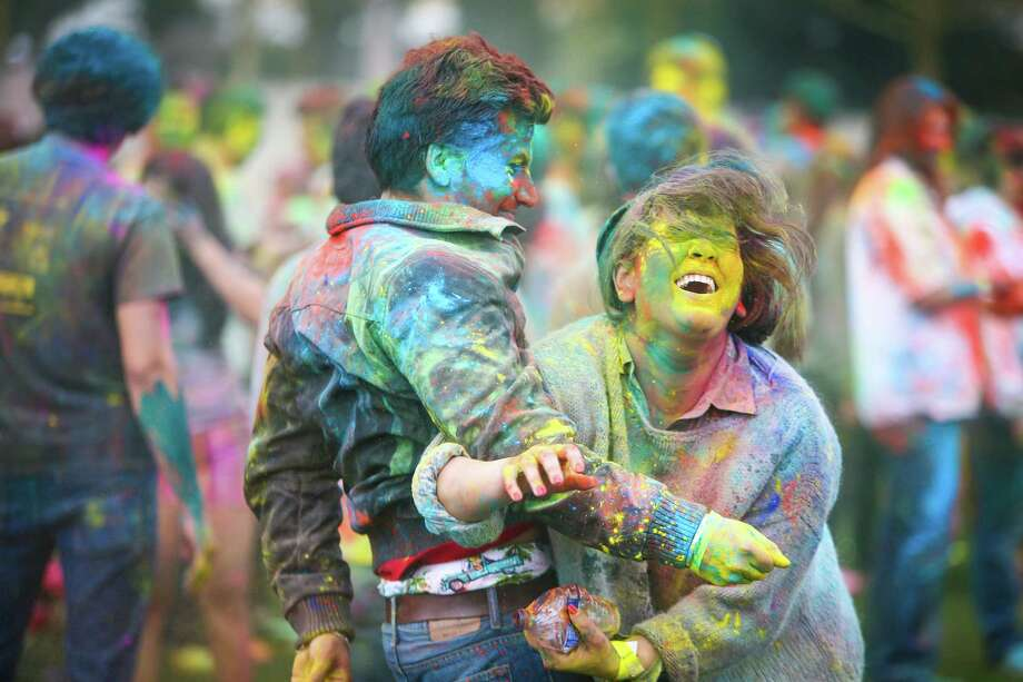 Participants wrestle over colored powder during the annual Holi celebration organized by the group Child Rights and You. The annual event celebrates the Indian festival of color and is a fundraiser for CRY. Holi recognizes the coming of spring with colored powder that people throw on each other. Photographed on Saturday, March 22, 2014 at Downtown Park in Bellevue. Photo: JOSHUA TRUJILLO, SEATTLEPI.COM / SEATTLEPI.COM