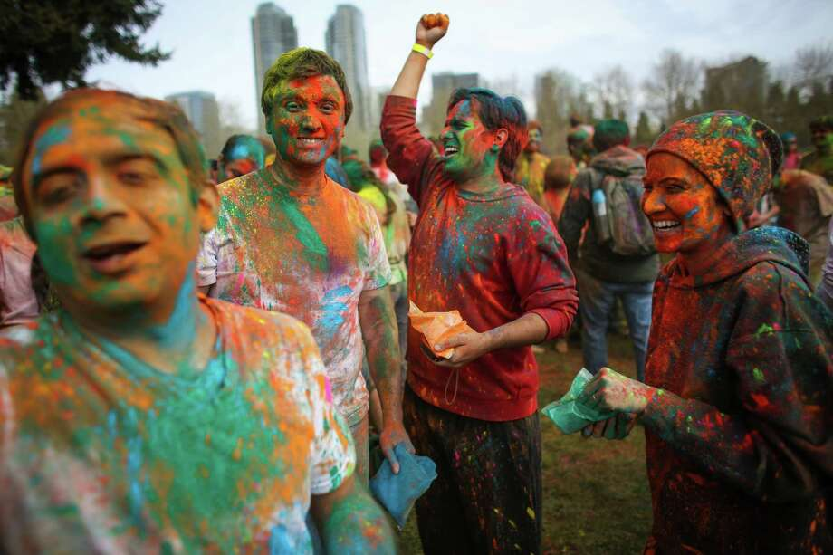 Participants dance with colored powder during the annual Holi celebration organized by the group Child Rights and You. The annual event celebrates the Indian festival of color and is a fundraiser for CRY. Holi recognizes the coming of spring with colored powder that people throw on each other. Photographed on Saturday, March 22, 2014 at Downtown Park in Bellevue. Photo: JOSHUA TRUJILLO, SEATTLEPI.COM / SEATTLEPI.COM