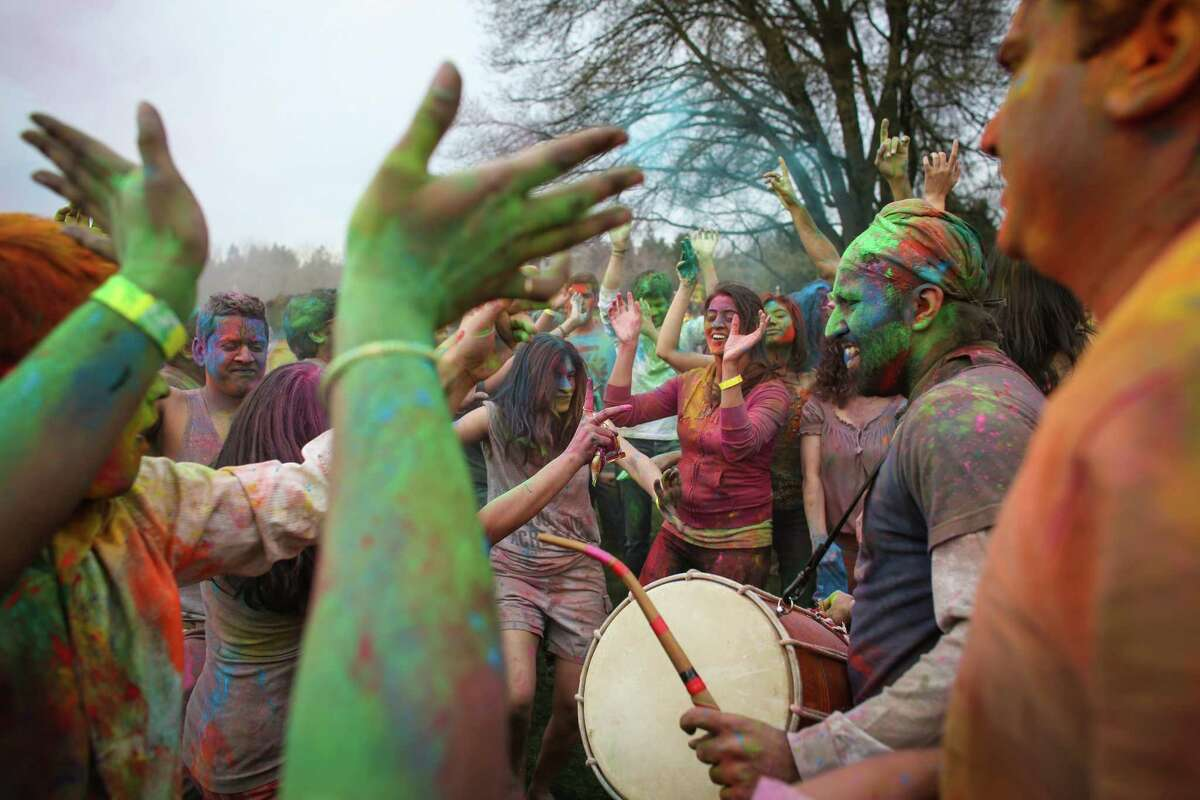 Participants dance to a drum during the annual Holi celebration organized by the group Child Rights and You. The annual event celebrates the Indian festival of color and is a fundraiser for CRY. Holi recognizes the coming of spring with colored powder that people throw on each other. Photographed on Saturday, March 22, 2014 at Downtown Park in Bellevue.