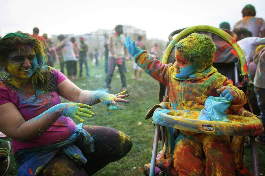 Yuvraj Gupta, 2, throws colored powder on Shikha Gandhi during the annual Holi celebration organized by the group Child Rights and You. The annual event celebrates the Indian festival of color and is a fundraiser for CRY. Holi recognizes the coming of spring with colored powder that people throw on each other. Photographed on Saturday, March 22, 2014 at Downtown Park in Bellevue. Photo: JOSHUA TRUJILLO, SEATTLEPI.COM / SEATTLEPI.COM