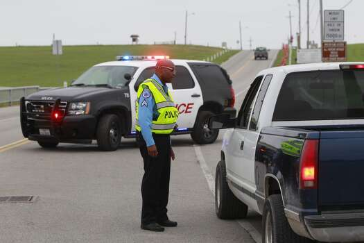 Texas City police Cpl. Mickey House mans a roadblock at the entrance of the Texas City Dike on Sunday, March 23, 2014. (Melissa Phillip / Houston Chronicle)
