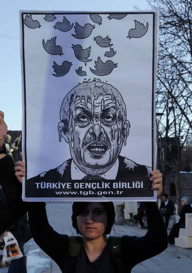 A member of the Turkish Youth Union holds up a cartoon depicting Turkey's Prime Minister Recep Tayyip Erdogan during a protest against a ban on Twitter, in Ankara, Turkey, Friday, March 21, 2014. Turkey's attempt to block access to Twitter appeared to backfire on Friday with many tech-savvy users circumventing the ban and suspicions growing that the prime minister was using court orders to suppress corruption allegations against him and his government. Photo: Burhan Ozbilici, AP / AP2014