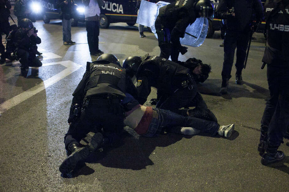 Police arrest a demonstrator during a protest against the government in Madrid, Spain, Saturday, March 22, 2014. Spanish police and protesters clashed during an anti-austerity demonstration that drew tens of thousands of people to central Madrid on Saturday. Police said in a statement six officers were injured and 12 people were arrested. Photo: Gabriel Pecot, AP / AP