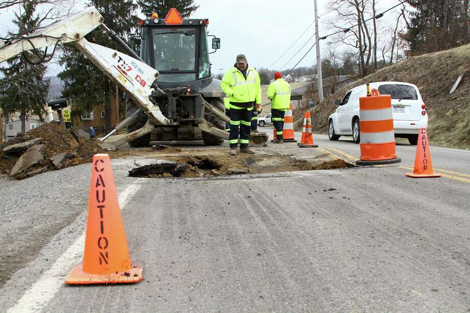 Workers inspect the sink hole on Pleasant Valley Road in Fairmont, W.Va., on Thursday, March 20, 2014. The hole was thought to be caused by mine subsidence. (AP Photo/Times West Virginian, Chelsi Baker) THE EXPONENT OUT; THE DOMINION-POST OUT. Photo: Chelsi Baker, AP / Times West Virginian