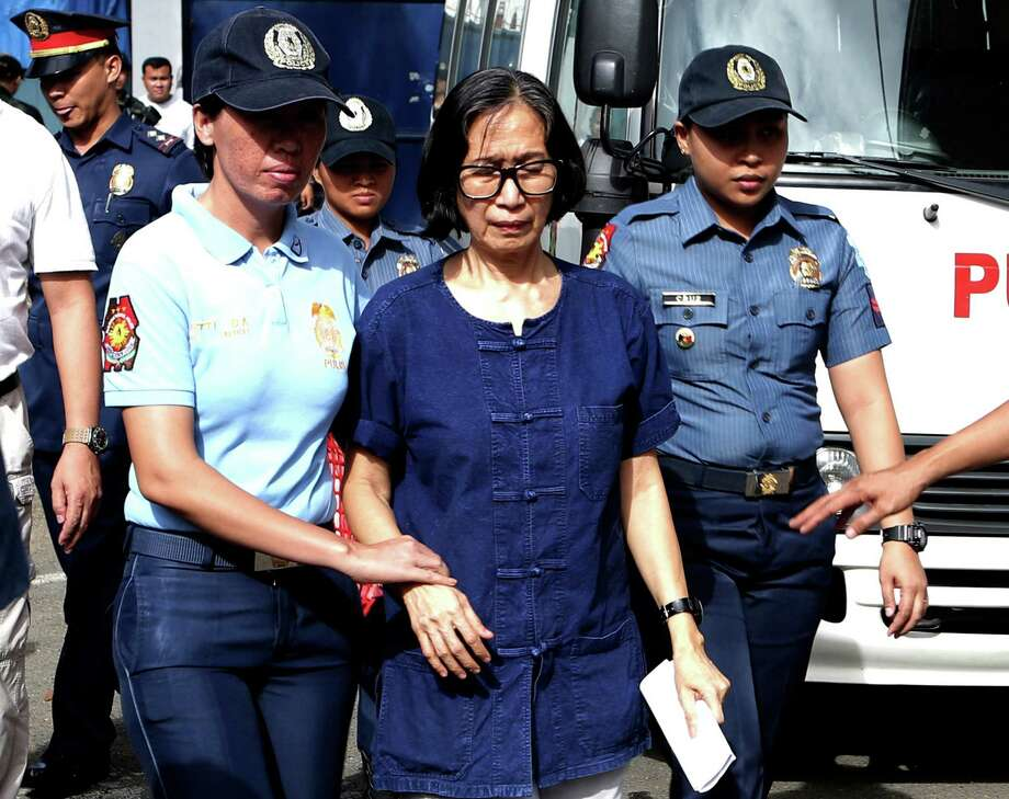 In this photo released by the Philippine National Police Public Information Office, suspected communist leader, Wilma Austria Tiamzon, is escorted as she arrives at the Camp Crame police headquarters in suburban Quezon city, north of Manila, Philippines on Sunday, March 23, 2014. Philippine officials said Sunday that they would not release two leaders of a violent rebel group fighting to overthrow the government, whose arrests were a serious blow to one of Asia's longest-running communist insurgencies. Photo: PHILIPPINE NATIONAL POLICE PUBLIC INFORMATION OFFICE, AP / Philippine National Police Public Information Office