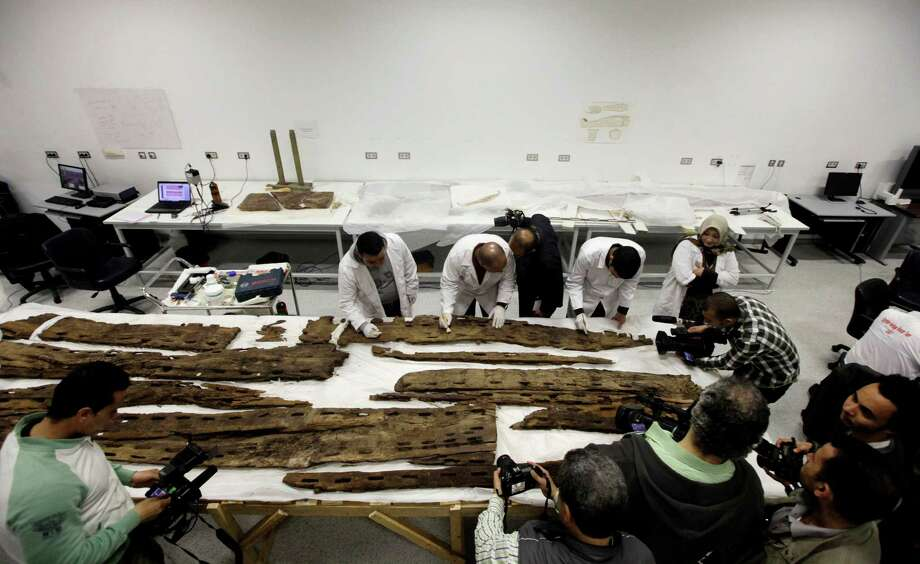 Egyptian conservators clean wooden parts of the early Dynastic period, boat of Abu Rawash, in the conservation center of Egypt's Grand museum under construction, just outside of Cairo, Egypt, Monday, March 17, 2014. Egypt's antiquities minister says construction has begun on the main hall of a massive new museum by the Pyramids, the final phase of a complex that's intended to house 100,000 ancient artifacts including King Tutankhamun's mummy. Photo: Amr Nabil, AP / AP2014