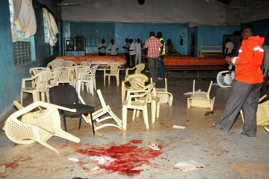 Blood stains on the church floor as Kenyan plaincloths police officer investigate inside Kenyan Joyland church  in Likoni,  near Mombasa, Kenya Sunday, March 23, 2014. Kenyan officials said  three people died after gunmen opened fire in a church just outside the coastal city of Mombasa. The Interior Ministry said Sunday that three gunmen opened fire inside the Joyland Church killing a small number of  people. At least 10  were wounded. Photo: Stringer, AP / AP