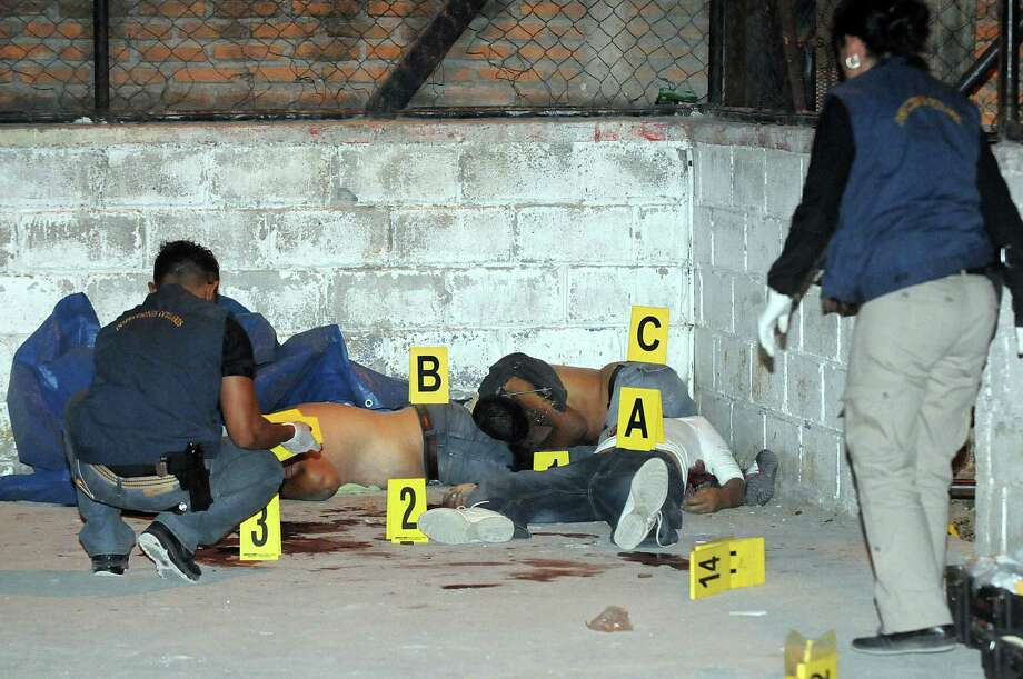 Investigators examine the bodies of three men that were killed by gunmen at a small soccer court in a village near the capital city of Tegucigalpa, Honduras, Wednesday March 19, 2014. Police said in a statement Thursday that the masked gunmen got out of their car, fired at the players and sped away. Five people were killed and three other players were wounded in the attack Wednesday night. Photo: Fernando Antonio, AP / AP