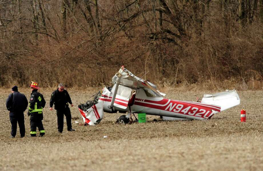 Emergency personnel look over a small plane that crashed southwest of the Combs and County Line Roads intersection Tuesday, March 18, 2014, in Greenwood, Ind. Police say a flight instructor and a student pilot were hurt when a small plane crashed in a farm field just south of Indianapolis. Photo: Scott Roberson, AP / The Daily Journal