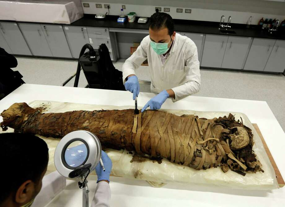 Egyptian conservators clean a female mummy dated to Pharaonic late period, (712-323 BC), in the conservation center of Egypt's Grand museum under construction, just outside Cairo, Egypt, Monday, March 17, 2014. Egypt's antiquities minister says construction has begun on the main hall of a massive new museum by the Pyramids, the final phase of a complex that's intended to house 100,000 ancient artifacts including King Tutankhamun's mummy. Photo: Amr Nabil, AP / AP2014