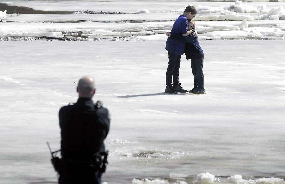 In this Thursday, March 20, 2014 photo, Corbin Crawford, 12, left, holds his brother, Dylan Crawford, 7, as the pair await rescue from the shifting ice above the Hydroelectric Dam on the Des Moines River near Fort Dodge, Iowa. The Fort Dodge Fire Department says the incident occurred Thursday afternoon near Hydro Electric Park. The boys got stuck on a sheet of ice about 75 feet from the west bank of the river. Fort Dodge Police officer Tim Breon talks to them at left. Photo: Hans Madsen, AP / The Messenger