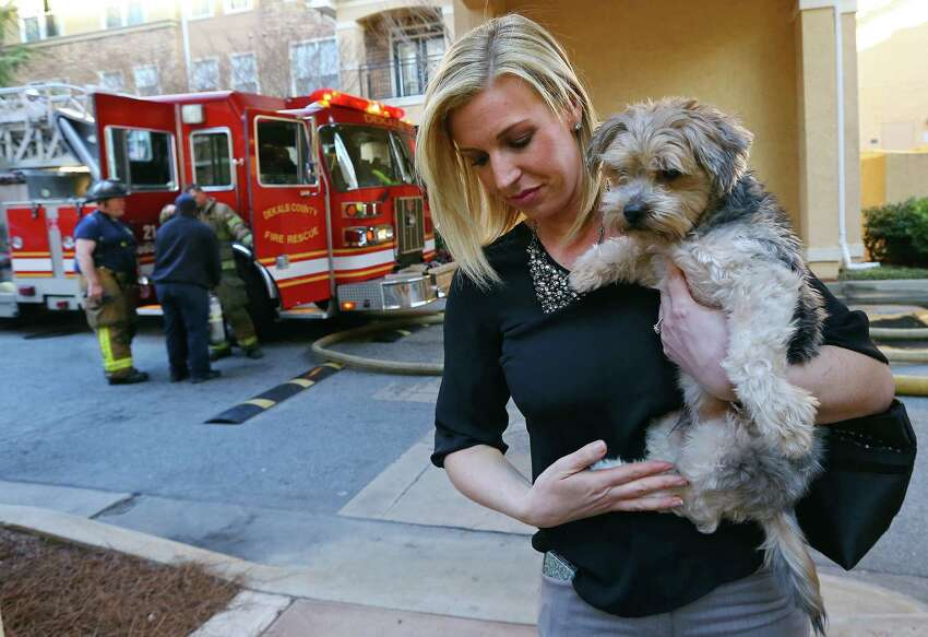 Mandy Peace embraces one of her two dogs Jethro outside a two-alarm apartment fire on Thursday, March 20, 2014, in Atlanta. Peace had firefighters kick in her door to rescue her dogs from her apartment after she arrived home from work to find the building on fire. There are no apparent injuries from the fire that forced the building to be evacuated. (AP Photo/Atlanta Journal-Constitution, Curtis Compton)