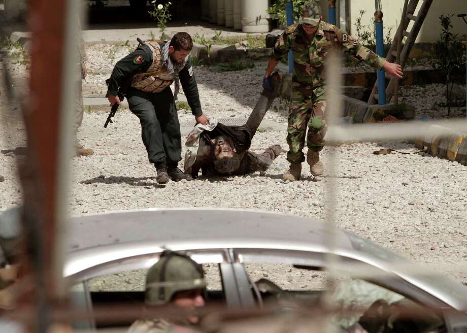 An Afghan Army solider and policeman drag the lifeless body of a suicide bomber from the scene after the Taliban staged a multi-pronged attack on a police station in Jalalabad, eastern Afghanistan, Thursday, March 20, 2014. Taliban insurgents staged the attack, using a suicide bomber and gunmen to lay siege to the station, government officials said. Two remotely detonated bombs also exploded nearby. Photo: Rahmat Gul, AP / AP2014