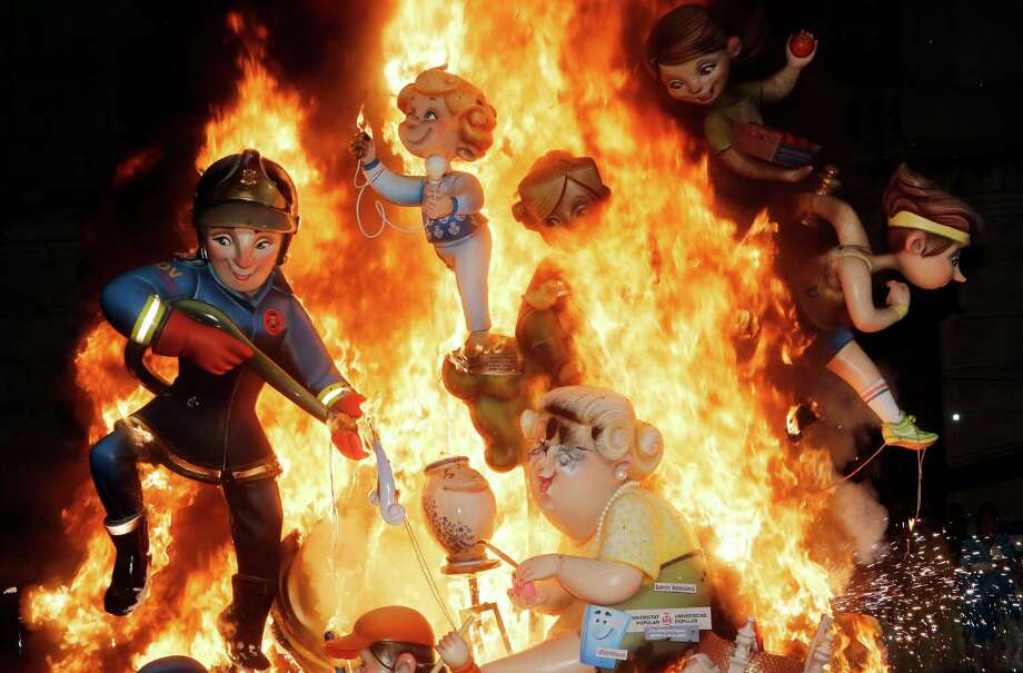 "Satirical sculptures burn during the traditional Fallas festival in Valencia, Spain, on Wednesday, March 19, 2014. Every year the city of Valencia celebrates the ancient ""Las Fallas"" fiesta, a noisy week that is full of fireworks and processions in honor of Saint Joseph that ends in the midnight of March 19, burning large satiric figures displayed around the streets of the city. Photo: Alberto Saiz, AP / AP2014"