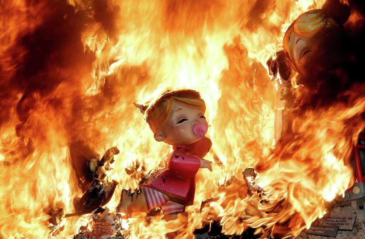 Satirical sculptures burn during the traditional Fallas festival in Valencia, Spain, on Wednesday, March 19, 2014. Every year the city of Valencia celebrates the ancient