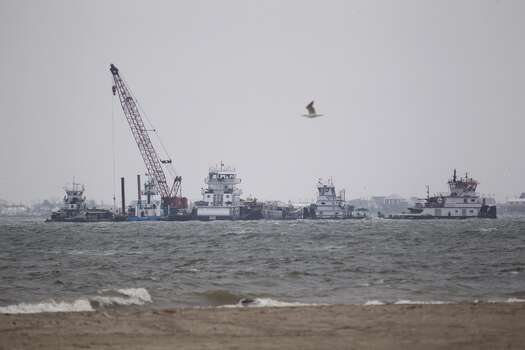 Emergency crews work along a barge that was struck by a ship shown near the Texas City Dike Sunday, March 23, 2014. (Melissa Phillip / Houston Chronicle)