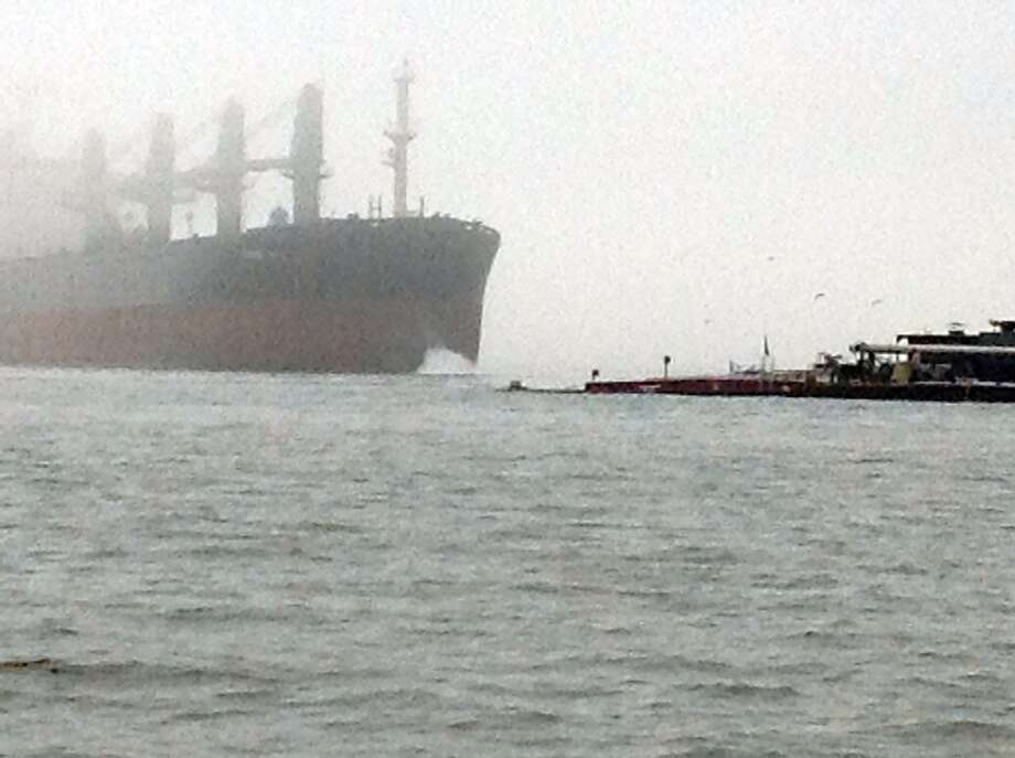 A reader caught this image of the ship spewing liquid soon after impact Saturday in the Texas City Dike area. (Janet Lee Knizner-Enders / For the Chronicle)