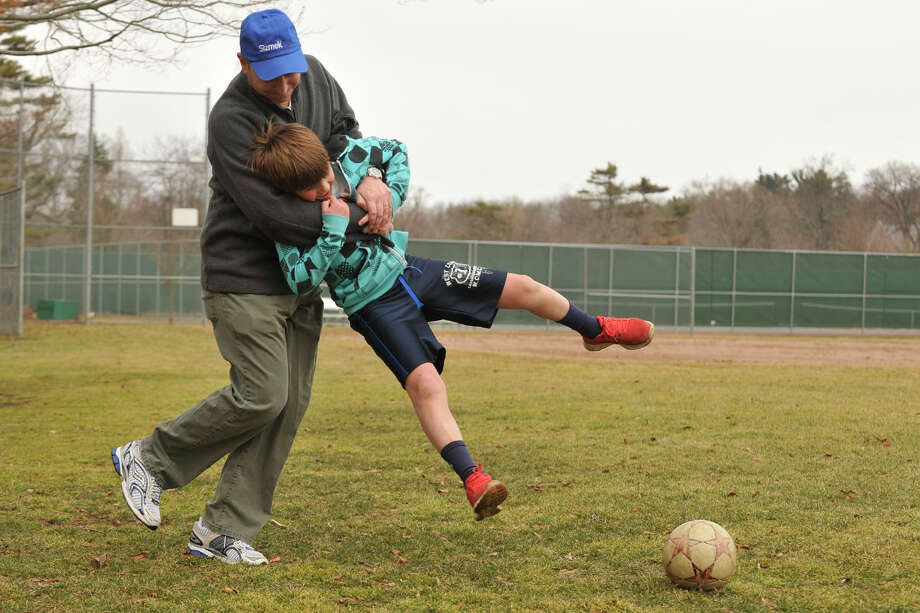 Andy Ellenthal swings his son, Ben, while kicking a soccer during a pick-up game of soccer with his other son, Sam, not pictured, at Binney Park in Old Greenwich, Conn., on Sunday, March 23, 2014. Photo: Jason Rearick / Stamford Advocate