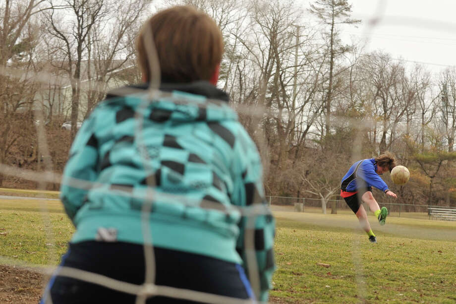 Sam Ellenthal, right, takes a penalty kick against his brother, Ben, who is guarding the goal as they play a pick-up game of soccer at Binney Park in Old Greenwich, Conn., on Sunday, March 23, 2014. Photo: Jason Rearick / Stamford Advocate