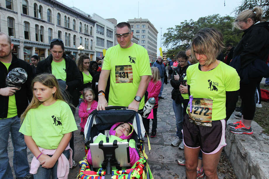 "From left, Mara Wheat, U.S. Army Major Larry Wheat, Cami Lundt and thirteen-year-old Kristina ""Krissy"" Krotzer in stroller, pray before the start of the Alamo 13.1 Half Marathon race, Sunday, March 23, 2014. Krotzer is affected Trisomy 18, a genetic disorder that causes physical defects and health issues. Wheat pushed Krotzer in the customized stroller. Photo: JERRY LARA, San Antonio Express-News / © 2014 San Antonio Express-News"