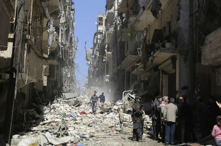 Syrian rebels and civilians inspect the damage from an air strike by government forces in Aleppo. Photo: Stringer, Reuters
