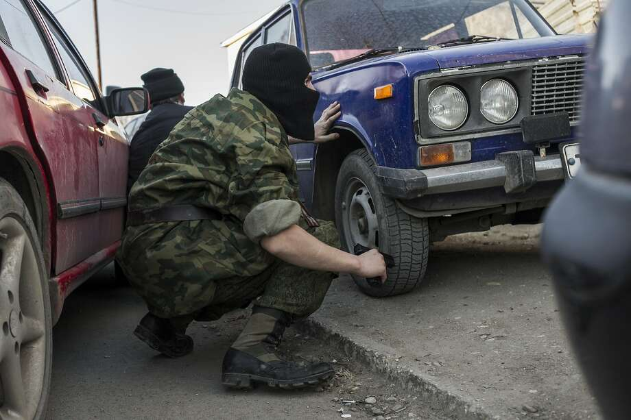 A pro-Russia militia member holds a gun while forces assault and take over the Belbek Air Force Base outside Sevastopol in Crimea. Ukraine is demanding the release of the base's commander. Photo: Andrew Lubimov, Associated Press
