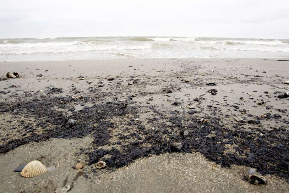 A black sticky oily substance is shown along the beach at the Texas City Dike near the barge spill cleanup site Sunday, March 23, 2014. Officials say the material is consistent with how oil could appear when it impacts beaches. However it would have to be analyzed to determine its origin.   (Melissa Phillip / Houston Chronicle)