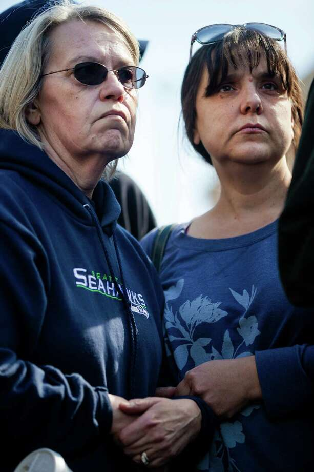 Barbara Welsh, left, a mudslide victim whose husband is still missing, holds hands with another woman, name not given, who has yet to hear from her uncle Sunday, March 23, 2014, during a outside of the Arlington Police Department in Arlington, Wash. Authorities say 18 people are unaccounted for after a massive mudslide killed at least three people and destroyed 30 homes, forcing evacuations from fears of the Stillaguamash River flooding. Photo: JORDAN STEAD, SEATTLEPI.COM / SEATTLEPI.COM