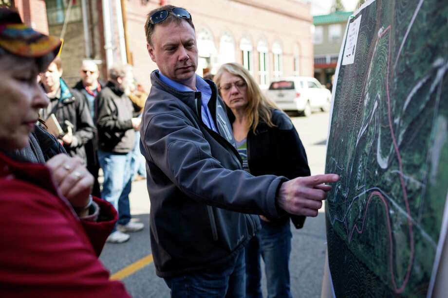 Snohomish County residents and media study a map of the mudslide area Sunday, March 23, 2014, outside of the Arlington Police Department in Arlington, Wash. Authorities say 18 people are unaccounted for after a massive mudslide killed at least three people and destroyed 30 homes, forcing evacuations from fears of the Stillaguamash River flooding. Photo: JORDAN STEAD, SEATTLEPI.COM / SEATTLEPI.COM