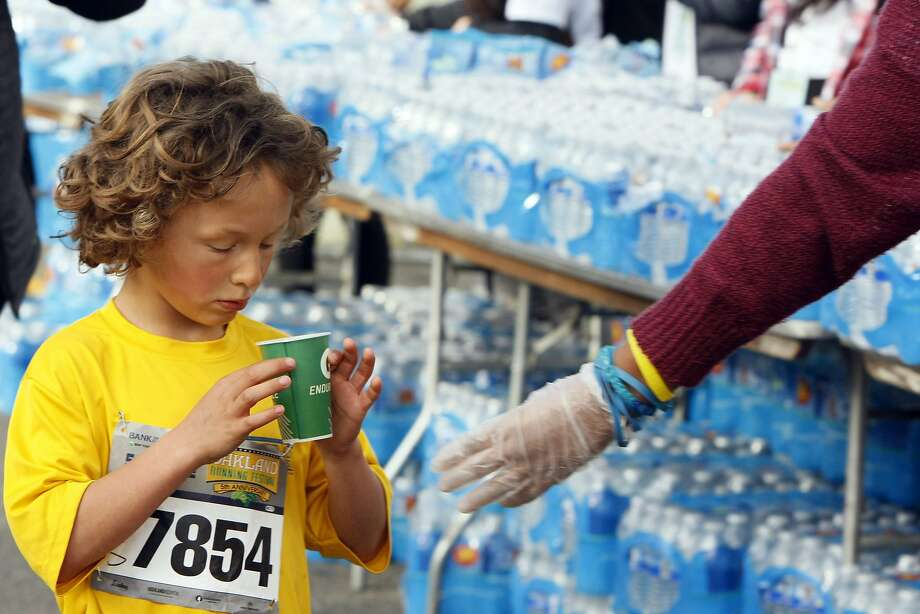 Zach Schoen, 7, (left) gets a glass of Gatorade from Ryan Gratton, 16, (rught) during the 5th annual Oakland Running Festival on March 23, 2014 in Oakland, Calif. Thousands of people of all ages came out to enjoy the day and participate in the various running events. Photo: Codi Mills, The Chronicle