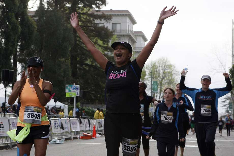 Loriece Dickerson, 50, throws her arms up in celebration while crossing the finish line of the 5k during the 5th annual Oakland Running Festival on March 23, 2014 in Oakland, Calif. Thousands of people of all ages came out to enjoy the day and participate in the various running events. Photo: Codi Mills, The Chronicle
