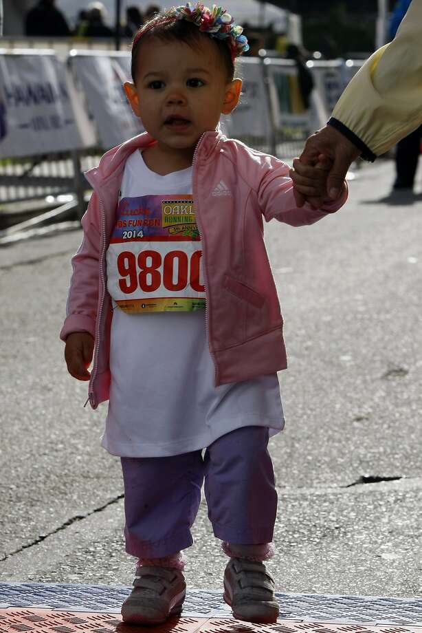 Safiya Duarte, 1, holds Ofelia Gutierrez's hand on the finish line after completing the kids' fun run during the 5th annual Oakland Running Festival on March 23, 2014 in Oakland, Calif. Thousands of people of all ages came out to enjoy the day and participate in the various running events. Photo: Codi Mills, The Chronicle