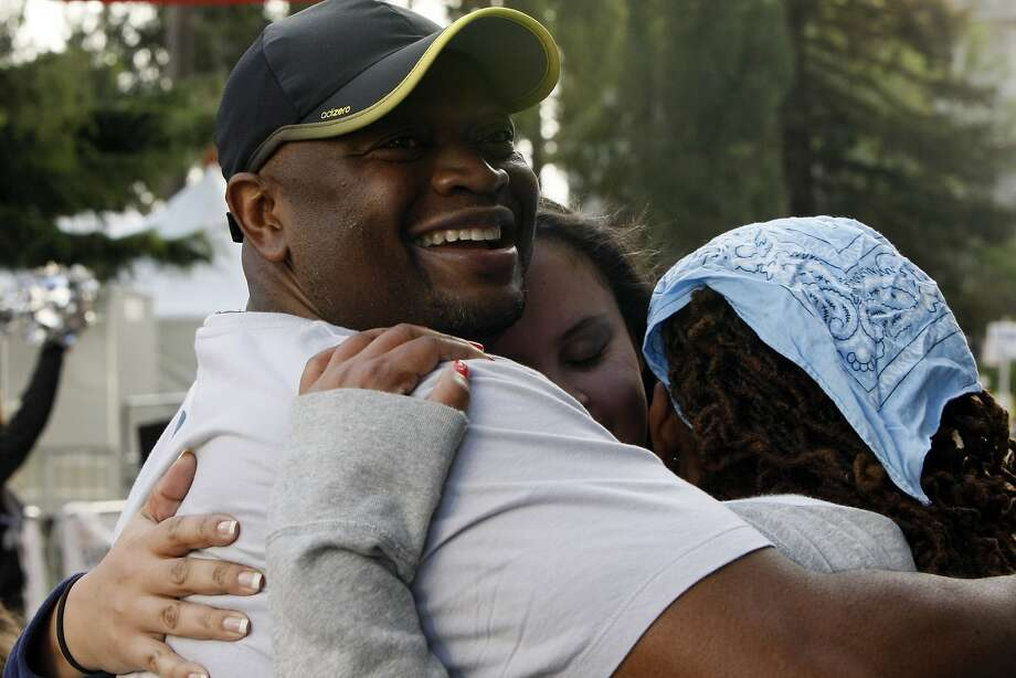Travis Mozeke, 46 (left), Jennifer Costa, 34 (center) and Keyona Lazenby, 36 (right) hug after completing their 5k during the 5th annual Oakland Running Festival on March 23, 2014 in Oakland, Calif. Thousands of people of all ages came out to enjoy the day and participate in the various running events. Photo: Codi Mills, The Chronicle