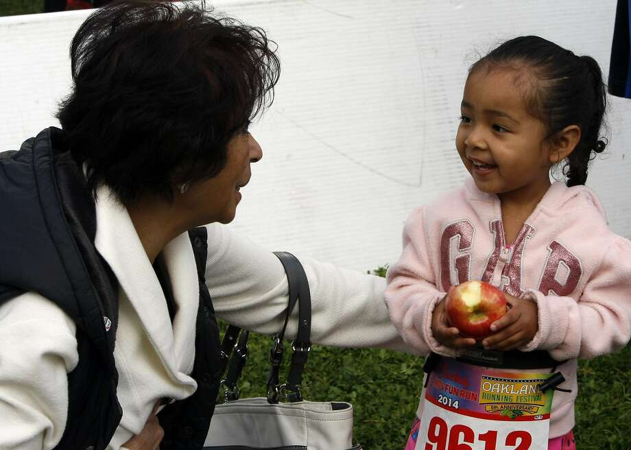 Etta Reyes (left) spends time with Sophia Reyes, 2, (right) before the younger participates in the kids' fun run during the 5th annual Oakland Running Festival on March 23, 2014 in Oakland, Calif. Thousands of people of all ages came out to enjoy the day and participate in the various running events. Photo: Codi Mills, The Chronicle