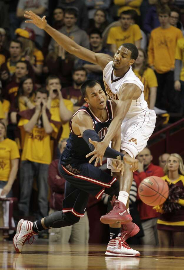 Stephen Holt, who had a game-high 24 points, passes around Minnesota's Austin Hollins. Photo: Paul Battaglia, Associated Press