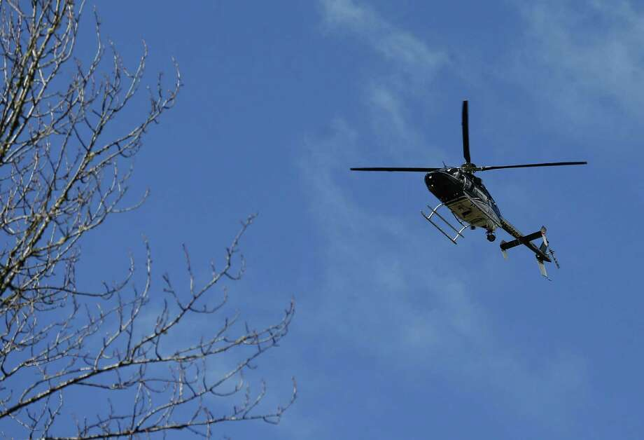 A Snohomish County Sheriff helicopter flies over the scene on Highway 530 next to mile marker 37 on Sunday, March 23, 2014, the day after a giant landslide occurred near mile marker 37 near Oso, Washington.  At least six homes have been washed away, with three people reported dead so far and at least eighteen missing. The nearby Stillaguamish River has been dammed up by 15-20 feet of debris as a result, creating more flooding concerns, as reported by KING 5 via the state hydrologist. Photo: Lindsey Wasson, AP / The Seattle Times Pool