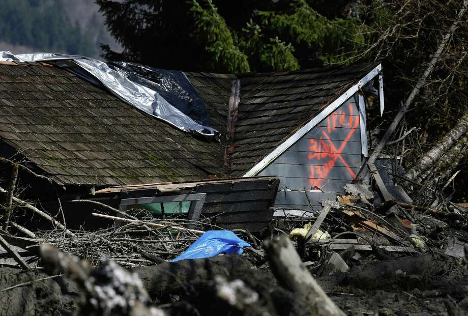 The orange X on a house, destroyed in the mud, indicates it has been searched for people on Highway 530, Sunday, March 23, 2014 the day after a giant landslide occurred near Oso, Wash. Rescue crews searched into the night for survivors from a massive mudslide that killed at least three people, after hearing voices from the debris field pleading for help. Photo: Lindsey Wasson, AP / Pool The Seattle Times
