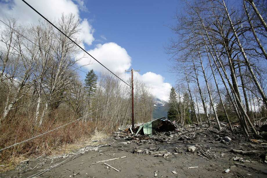 A destroyed house and downed power lines lie in the mud on Highway 530, Sunday, March 23, 2014 the day after a giant landslide occurred near Oso, Wash. The slide of mud, trees and rocks happened about 11 a.m. Saturday morning. Several people - including an infant - were critically injured and at least six houses were destroyed. Photo: Lindsey Wasson, AP / Pool The Seattle Times